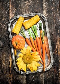 Cibo organico. raccolto fresco di verdure. su uno sfondo di legno.