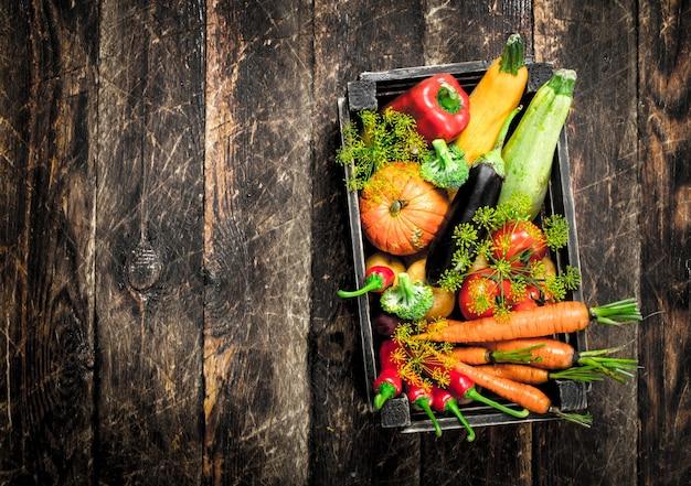 Cibo organico. raccolto fresco di verdure su un tavolo di legno.
