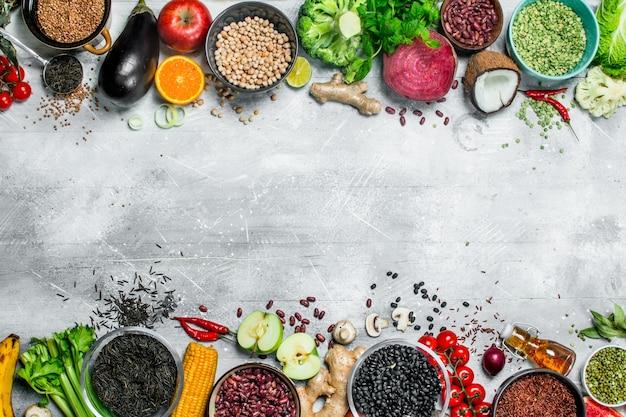Cibo organico. un sano assortimento di frutta e verdura con legumi. su un tavolo rustico.