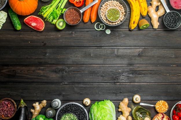Cibo organico. un sano assortimento di frutta e verdura con legumi. su uno sfondo di legno.