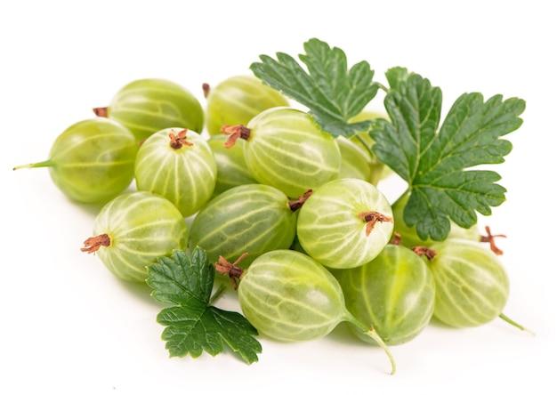 Alimento biologico, cibo sano, frutti di uva spina verde con foglia su bianco