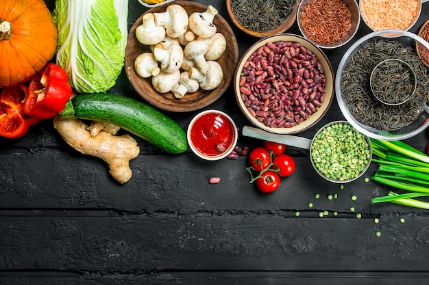 Cibo organico. varietà di frutta e verdura sana con legumi su un tavolo rustico nero.
