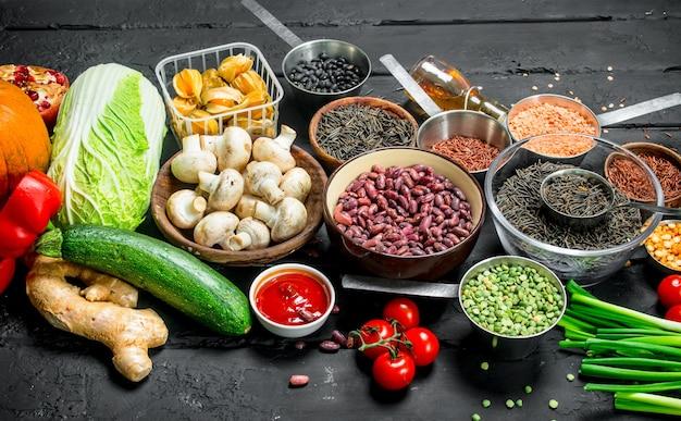 Cibo organico. varietà di frutta e verdura sana con legumi. su un rustico nero.