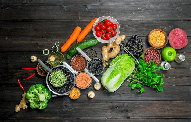 Cibo organico. varietà di frutta e verdura sana con legumi su un tavolo rustico.