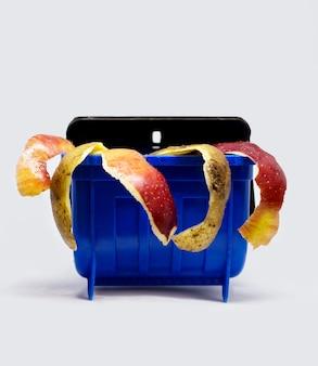 Rifiuti alimentari organici, bucce di patate e mele nel contenitore della spazzatura di plastica
