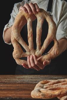 Pane fougas fresco biologico nelle mani uomo su sfondo nero