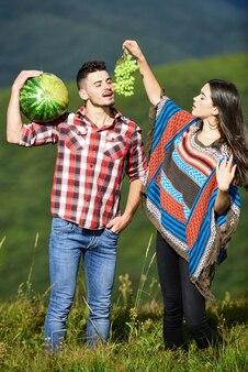 Biologico e sano. coppia hippie con frutta. vitamina e dieta. cibo estivo. l'uomo e la donna tengono l'anguria. ragazza e ragazzo mangiano l'uva. raccolto estivo. weekend in famiglia all'aperto. vacanze estive.