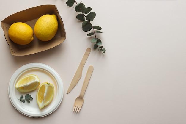 Stoviglie organiche e due contenitori con limoni su fondo beige chiaro, vista dall'alto