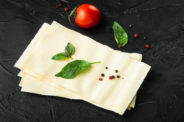 Sfoglie di pasta lasagna bio condite ed erbe su pietra nera