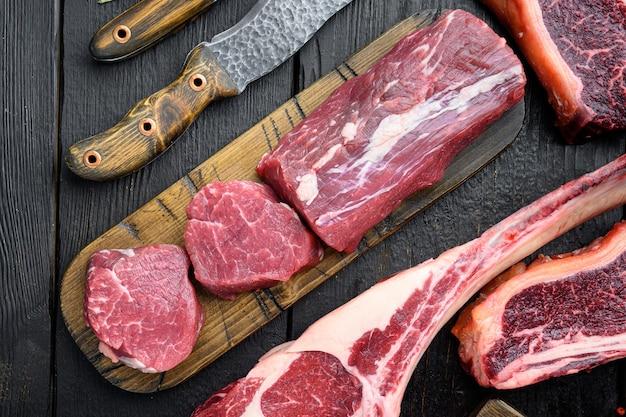 Bistecca di carne di manzo marmorizzata organica e set di condimenti, filetto di filetto mignon tagliato, sul tagliere di legno, sul tavolo di legno nero