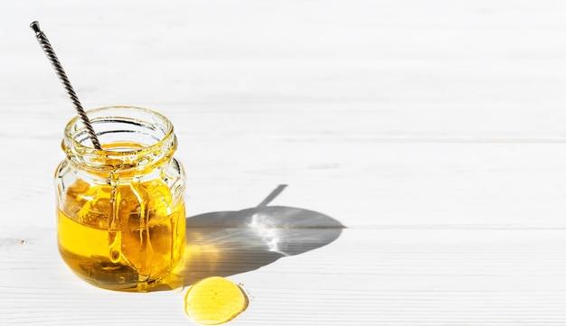 Miele naturale biologico in un barattolo di vetro su una superficie di legno bianca