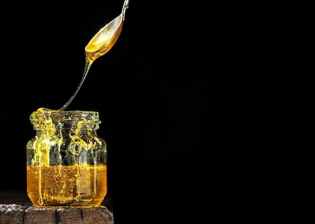 Miele naturale biologico, illuminato dalla luce solare, in un barattolo di vetro