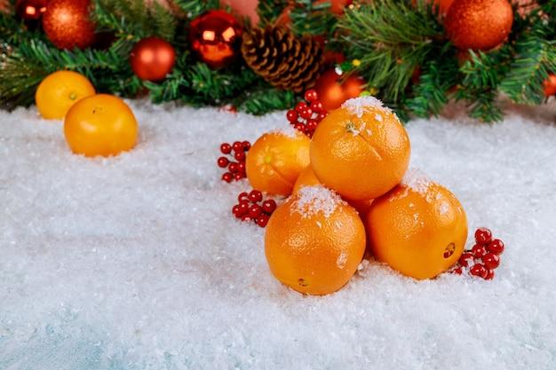 Ornamento di natale di pentecoste di arance biologiche sul bianco della neve.