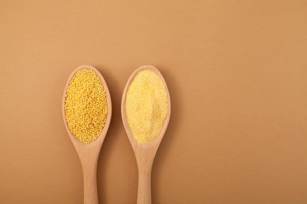 Farina e grano di miglio sbucciato sbucciato organico in cucchiai di legno su fondo beige