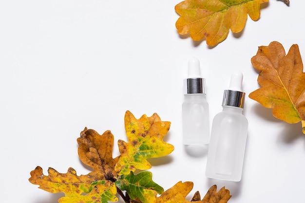 Sieri biologici per la cura della pelle e foglie autunnali luminose su sfondo bianco