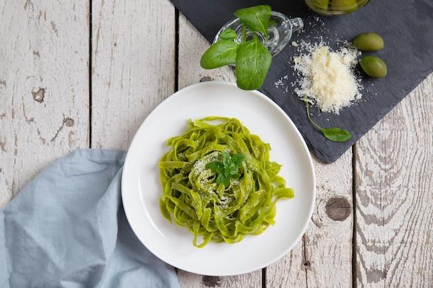 Pasta di fettuccine di spinaci bio, formaggio, foglia di basilico. superficie in legno bianco. vista dall'alto