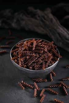 Fusilli di grano saraceno bio crudi su superficie scura. tagliatelle integrali senza glutine. concetto di cibo sano.