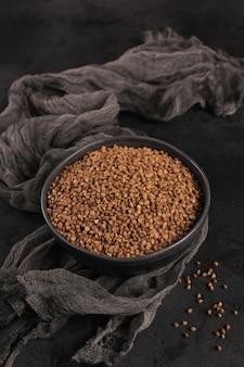 Chicchi di grano saraceno sparsi crudi organici in una ciotola su uno sfondo nero. concetto di cibo sano e dietetico.
