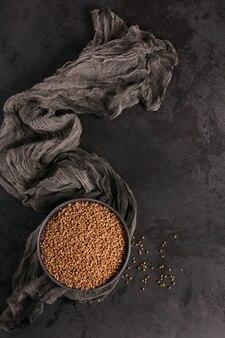 Chicchi di grano saraceno sparsi crudi organici in una ciotola sulla tavola nera. concetto di cibo sano e dietetico. vista dall'alto.