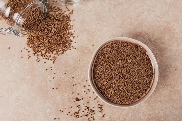 Chicco di grano saraceno sparsi crudo biologico in una ciotola e un barattolo di vetro su sfondo beige chiaro. concetto di cibo sano e dietetico. vista dall'alto