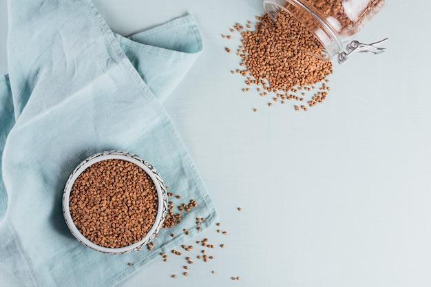 Chicco di grano saraceno sparsi crudo biologico in una ciotola e un barattolo di vetro sulla superficie azzurra. concetto di cibo sano e dietetico. vista dall'alto, piatto laico