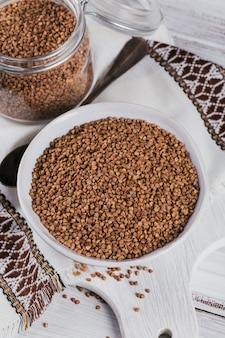Chicchi di grano saraceno sparsi crudi organici in una ciotola e vaso di vetro su un fondo rustico in legno bianco. concetto di cibo sano e dietetico.