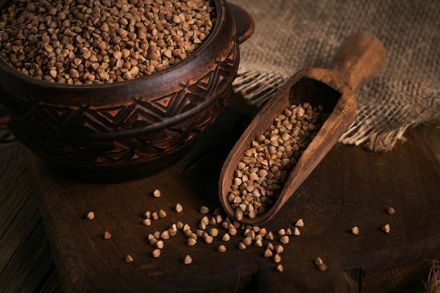 Chicchi di grano saraceno sparsi crudi organici in una ciotola e cucchiaio di legno su fondo di legno rustico