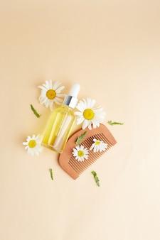 Cosmetici naturali bio vegani per capelli. composizione flat lay di fiori di camomilla e flaconi cosmetici con olio essenziale. bellezza naturale. vista dall'alto. spazio per il testo