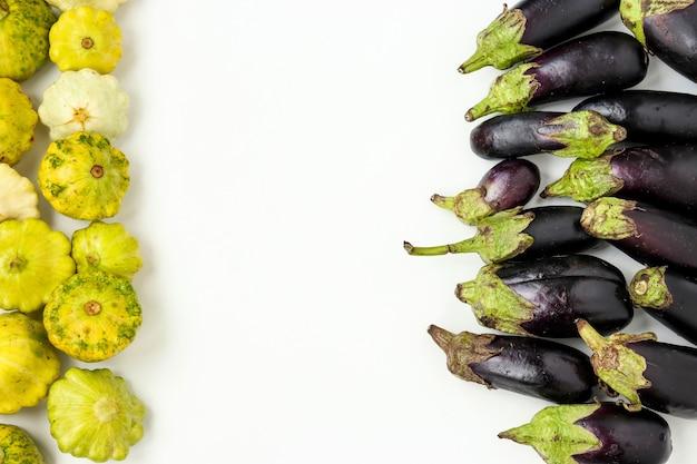 Verdure biologiche: patissons e melanzane su sfondo bianco, concetto di cibo biologico, orientamento orizzontale, spazio copia, vista dall'alto