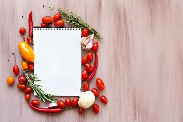 Verdure biologiche sulla tavola di legno. libro di ricette