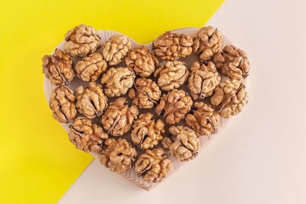 Le noci biologiche hanno la forma di un cuore. concetto di cibo sano