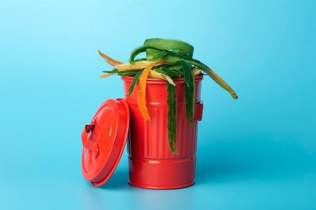 Rifiuti organici in un cestino rosso. riciclaggio e smistamento di rifiuti, cibo e rifiuti organici.