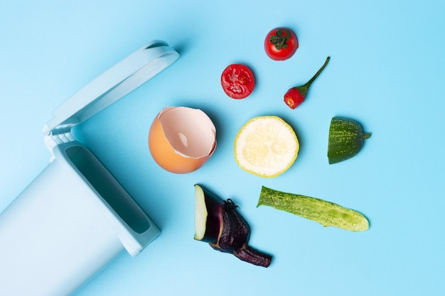 Rifiuti organici e pattumiera su uno sfondo blu, il concetto di raccolta differenziata