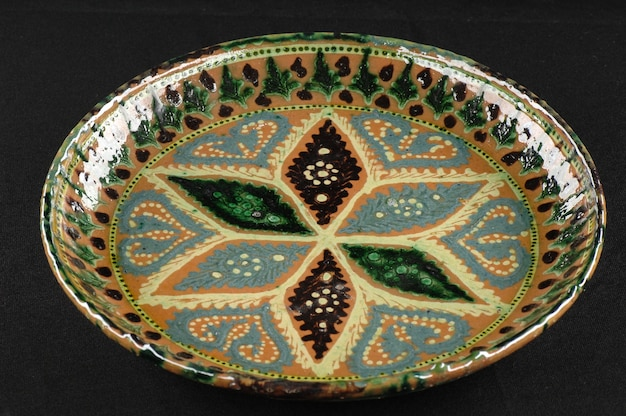 Piatto di ceramica antico orientale su un primo piano nero del fondo