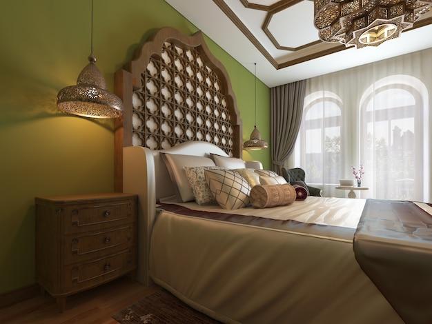 Camera da letto orientale in stile arabo, con testiera in legno e pareti verdi. mobile tv, specchiera, poltrona con tavolino. rappresentazione 3d.