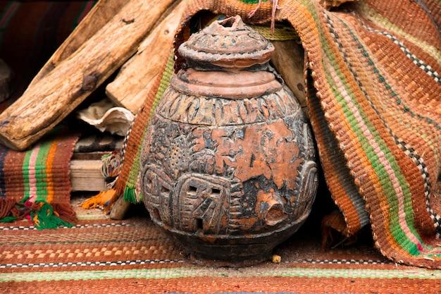 Brocca di ceramica orientale con ornamento sulla piazza del mercato si erge su tappeti etnici marroni intrecciati