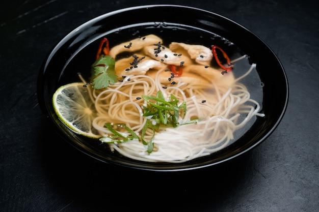 Cibo della cucina orientale. pasto tradizionale. noodle e zuppa di carne in una ciotola con verdure