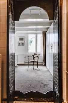 Design orientale della porta di legno segreta con persiane aperte, sala di visualizzazione con sedia alla luce del giorno