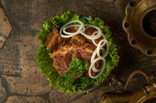 Piatti orientali su vecchie piastrelle decorative. carne fritta e brocca su vecchie pietre decorative per lastricati