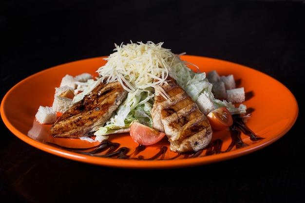 Insalata orientale con pollo su un piatto arancione, bella porzione, superficie scura.