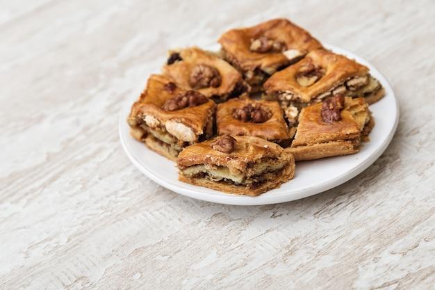 Baklava orientale dei dolci con miele e la noce sul piatto bianco. dessert orientale saporito su fondo di legno con lo spazio della copia