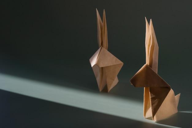 Coniglio di carta origami sotto il sole splendente con ombre dure. mestieri di carta. il concetto minimale di pasqua o l'anno del coniglio. il gioco di luci e ombre.