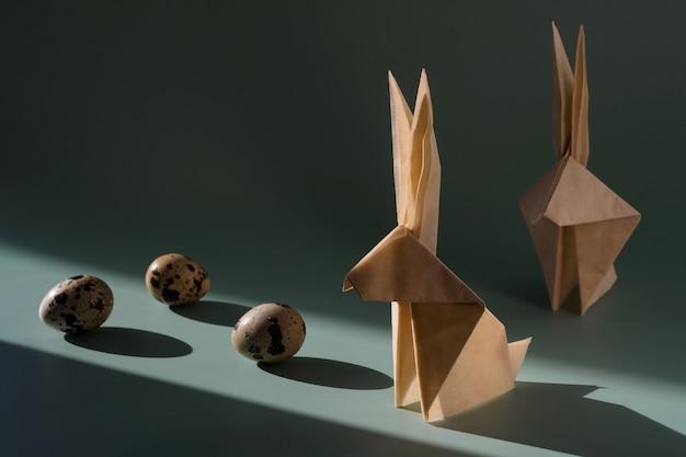 Coniglio di carta origami, uova di quaglia sotto il sole splendente con ombre dure. moderno e minimalista concetto di pasqua. sfondo luminoso di pasqua.