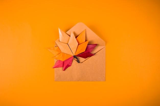 Lettera delle foglie cadute di concetto di autunno del papercraft di origami in una busta su un'arte fatta a mano del mestiere del fondo arancio