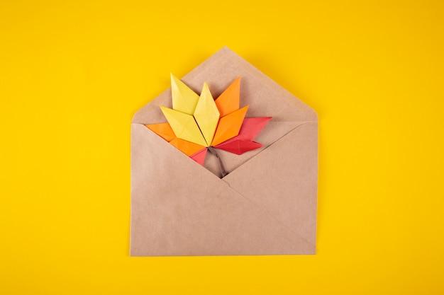 Lettera delle foglie cadute di concetto di autunno del papercraft di origami in una busta su un'arte fatta a mano del mestiere del fondo giallo