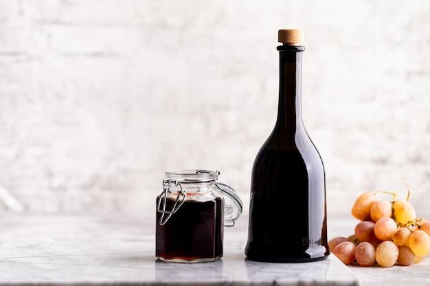 Bottiglie di vetro originali con aceto diverso su un tavolo di marmo contro un tavolo di un muro di mattoni bianchi. copia spazio. orizzontale.