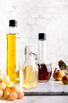 Bottiglie di vetro originali con aceto diverso su un tavolo di marmo contro un tavolo di un muro di mattoni bianchi. copia spazio. verticale.