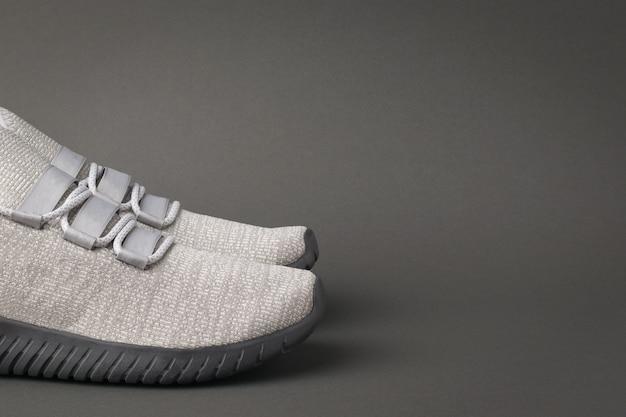 Originale sneakers sportive grigie su sfondo grigio scuro. stile di vita sportivo.