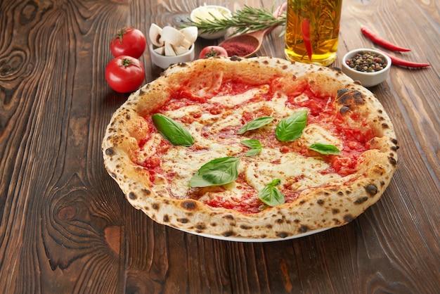 Pizza margherita italiana originale napoletana con mozzarella fusa foglie di basilico fresco e salsa di pomodoro su tavola di legno con ingredienti menu italiano fast food e concetto di mangiare vegetariano