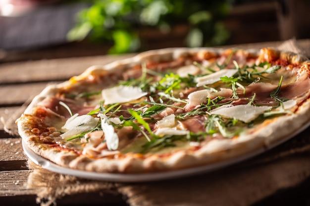 Pizza italiana originale con prosciutto, parmigiano e foglie di rucola.